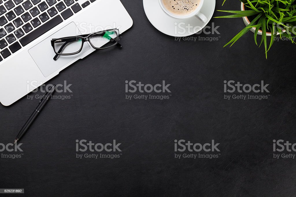 Office desk with laptop, coffee, plant stock photo