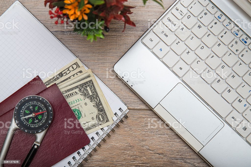 Office desk with laptop, money, passports, notebook and compass stock photo