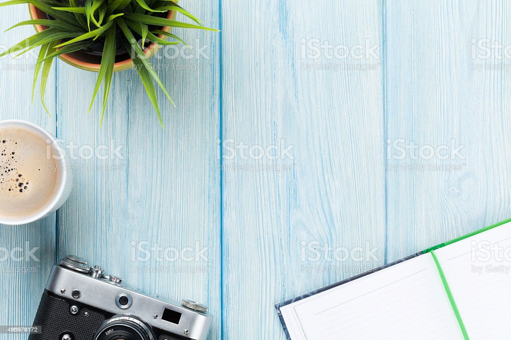 Office desk with notepad, camera, coffee and flower stock photo