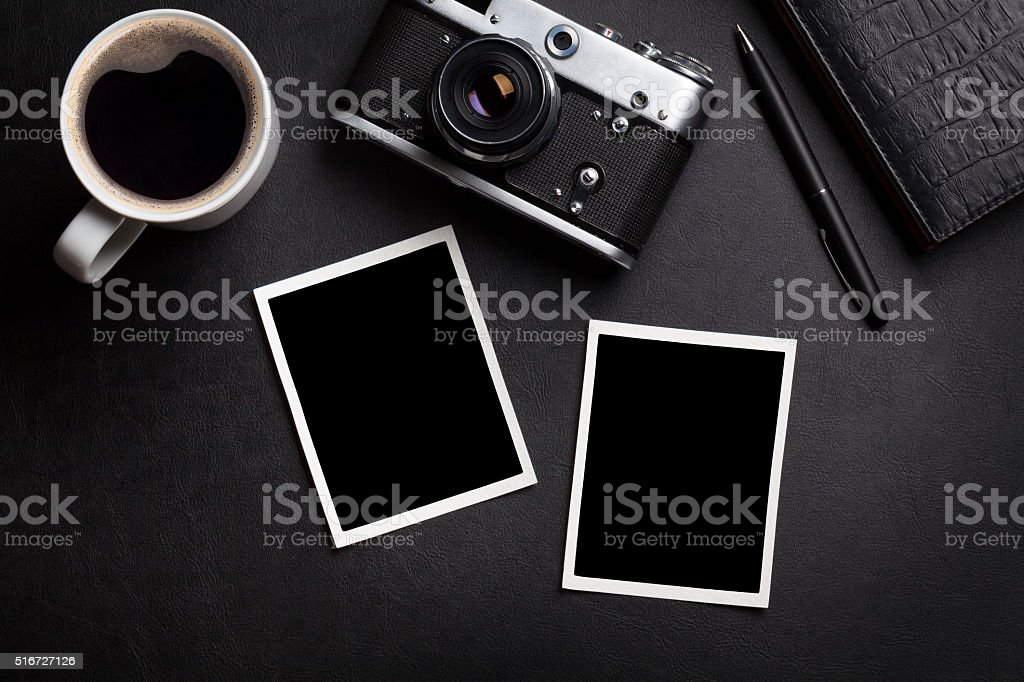 Office desk with photos, camera, coffee and notepad stock photo