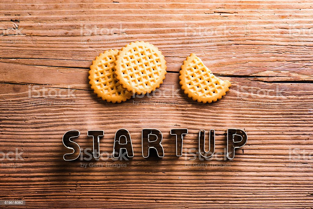 Office desk with start up sign and biscuits stock photo