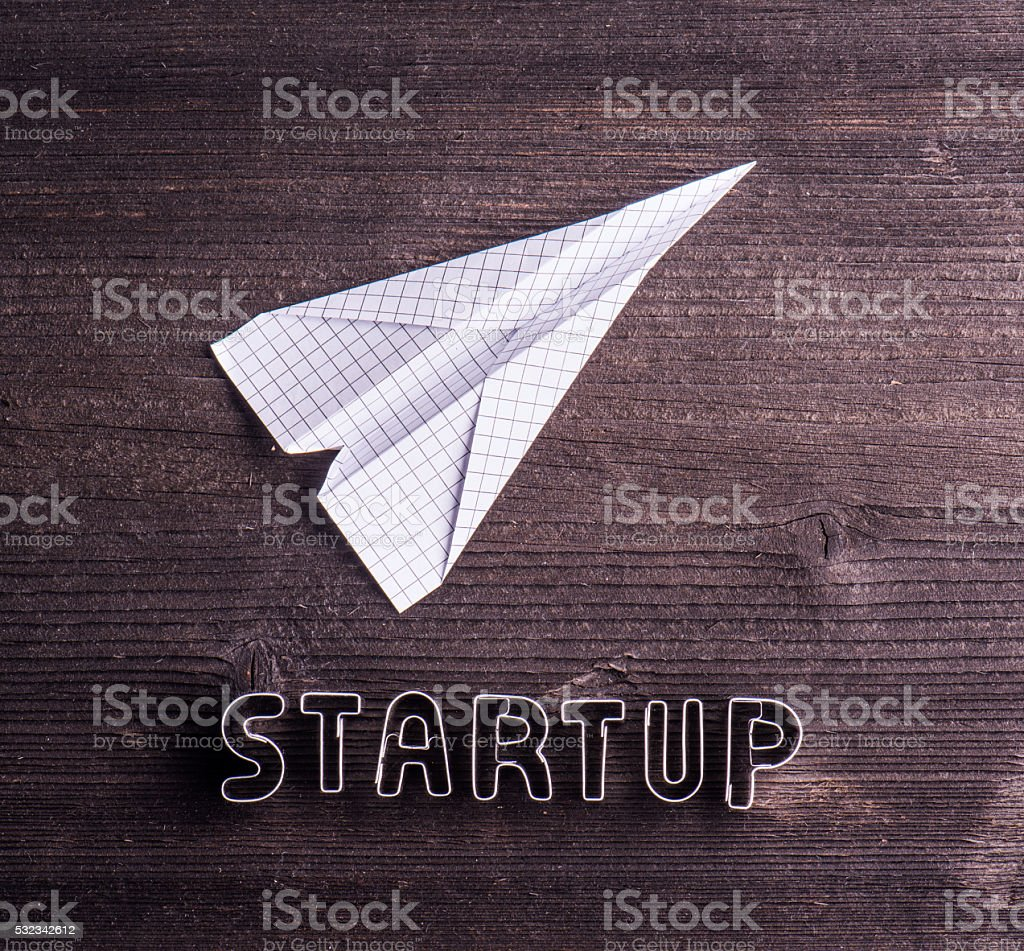 Office desk with start up sign and paper plane. stock photo