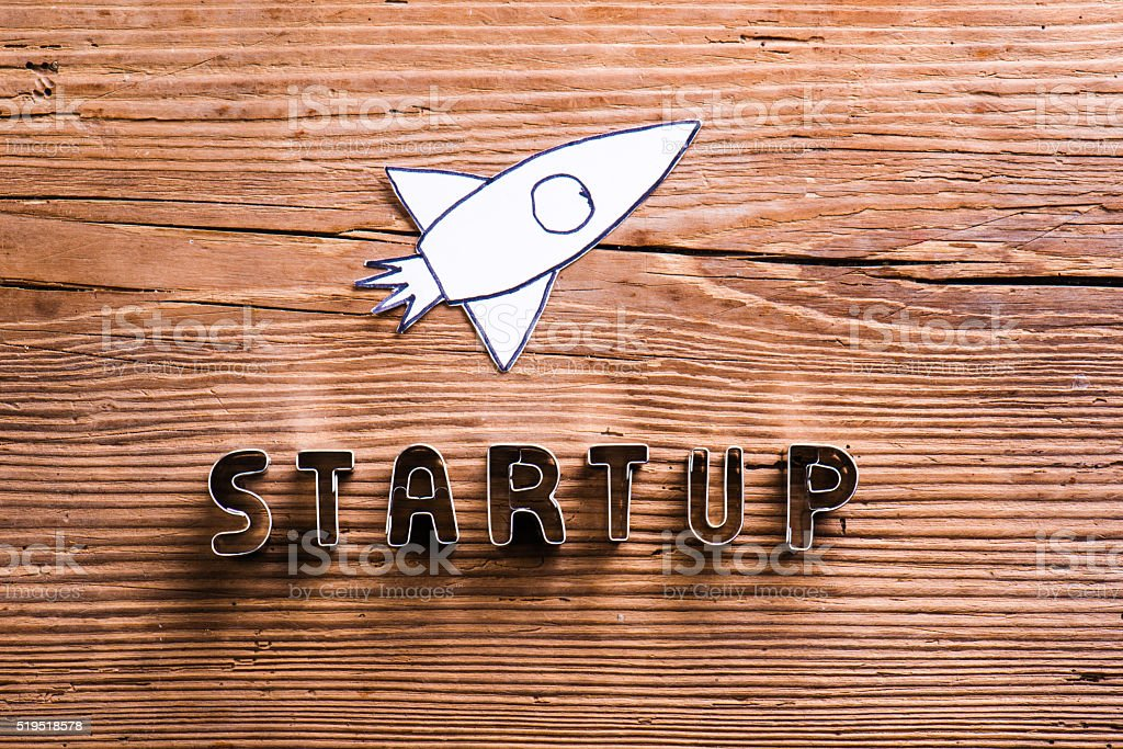 Office desk with start up sign and paper rocket. stock photo