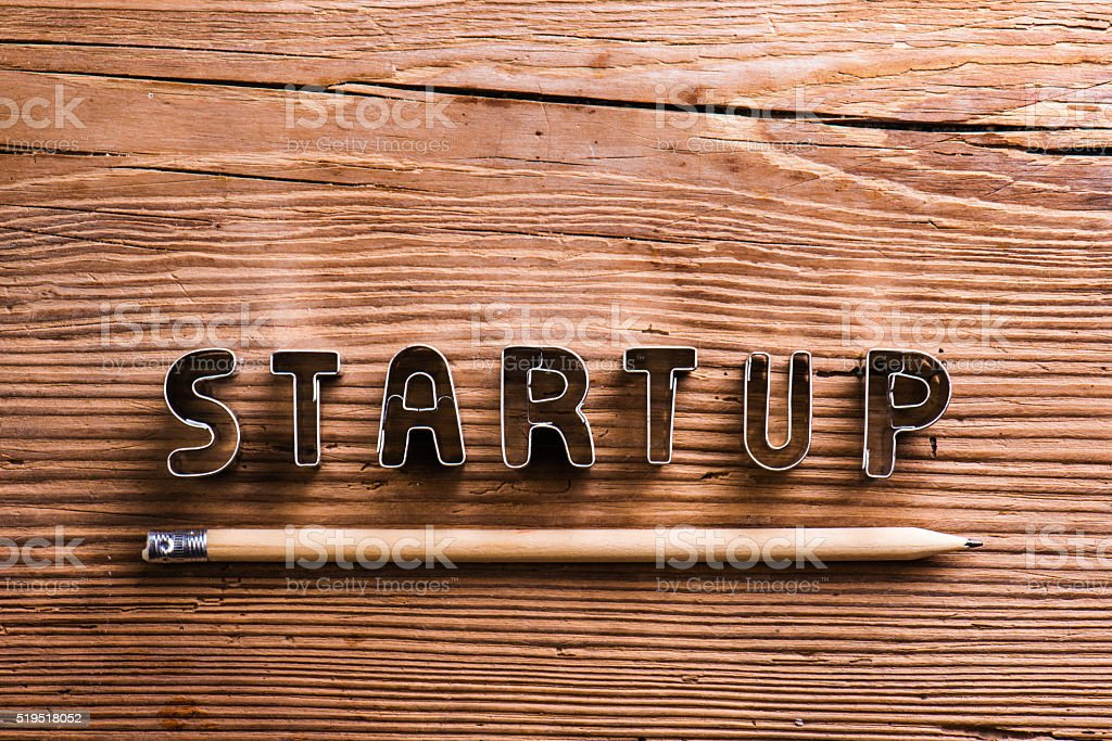 Office desk with start up sign and pencil. stock photo