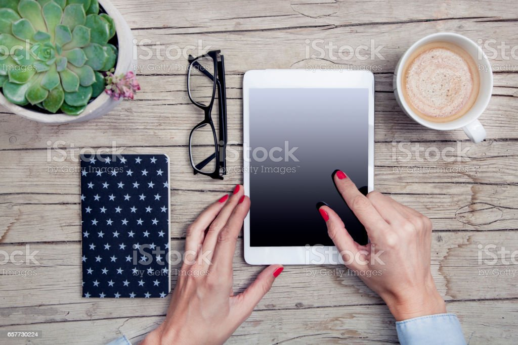 office desk with tablet, handy, notepad and cup of coffee
