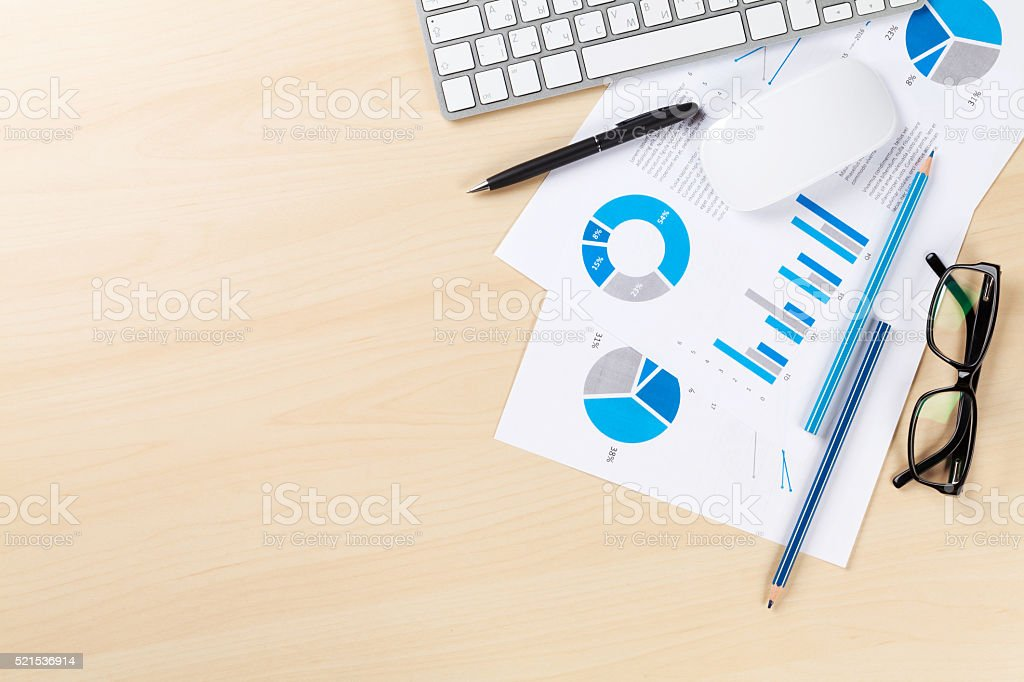 Office desk workplace with pc and charts stock photo