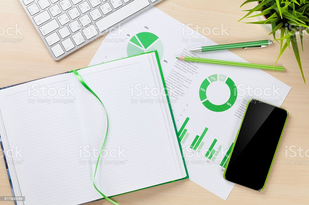 Office desk workplace with phone, charts and notepad stock photo