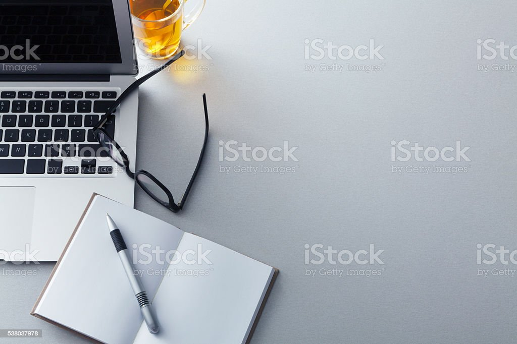Office: Desktop with Laptop, Tea, Glasses, Notebook and Pen stock photo