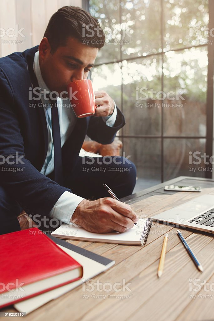 Office employee doing work and drink coffee stock photo