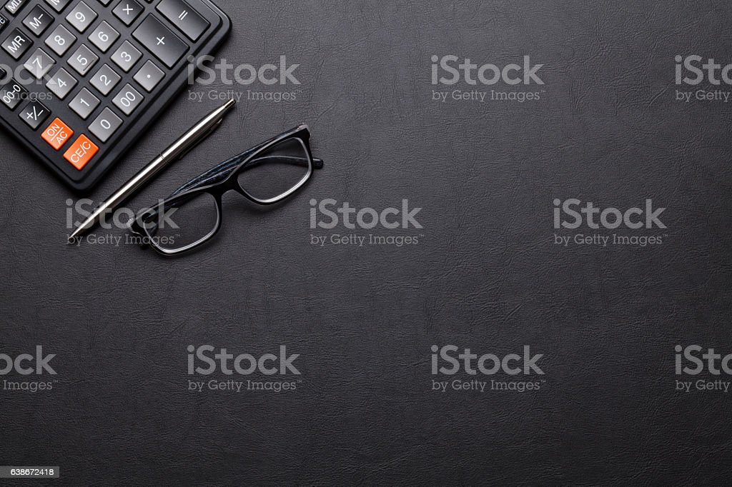 Office leather desk table with calculator, pen and glasses stock photo