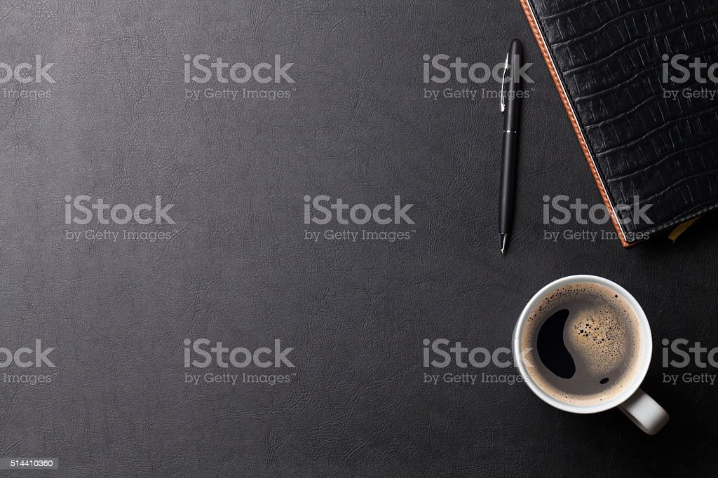 Office leather desk table with coffee and supplies stock photo