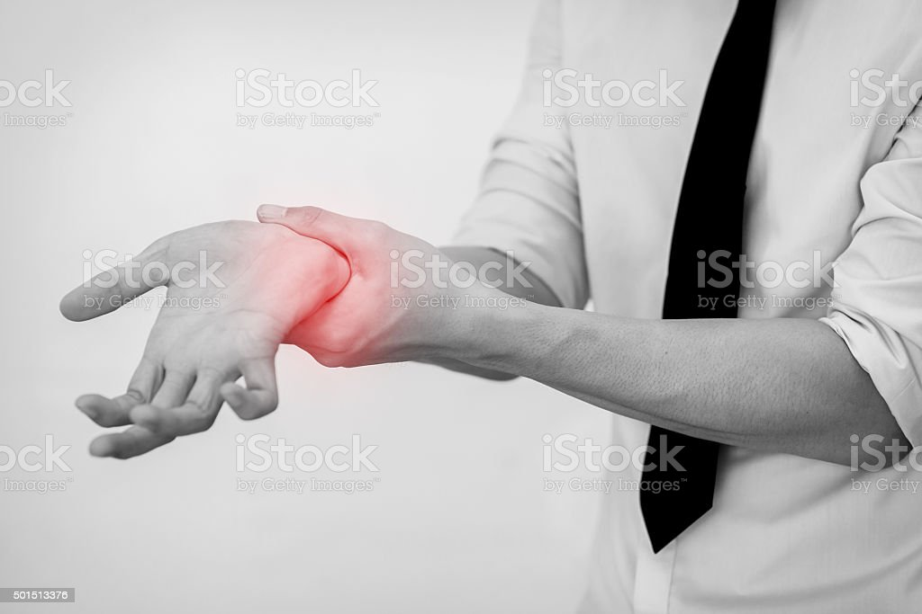 Office Man touching painful wrist.  (Focus on wrist) stock photo