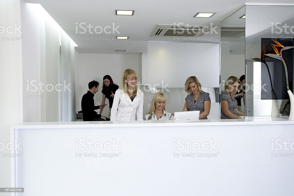 Office managers at reception desk using computer royalty-free stock photo