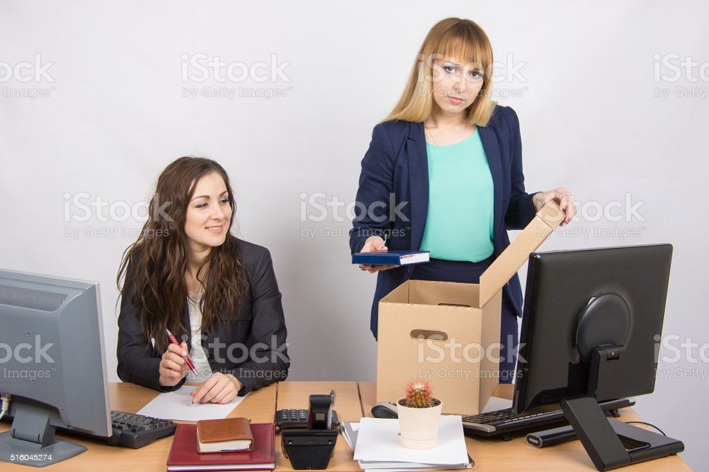 Office staff member with a smile watching charges fired colleagues stock photo