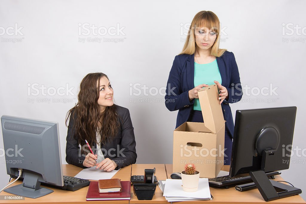 Office staff member with a smile watching fired colleague stock photo