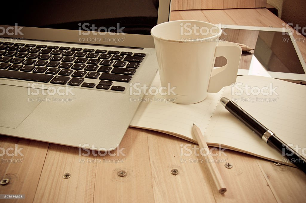 Office supplies with coffee cup and laptop in the office stock photo