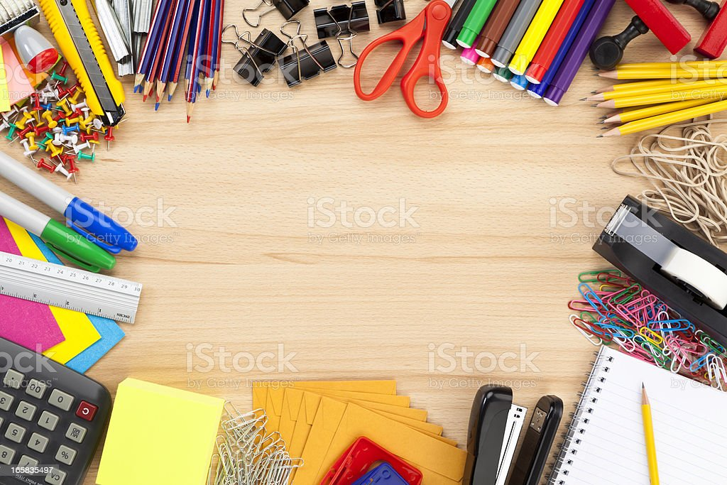 Office supply border on wood desk top shot directly above stock photo