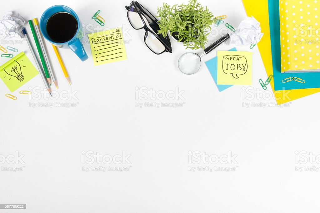 Office table desk with green supplies, blank note pad, cup stock photo