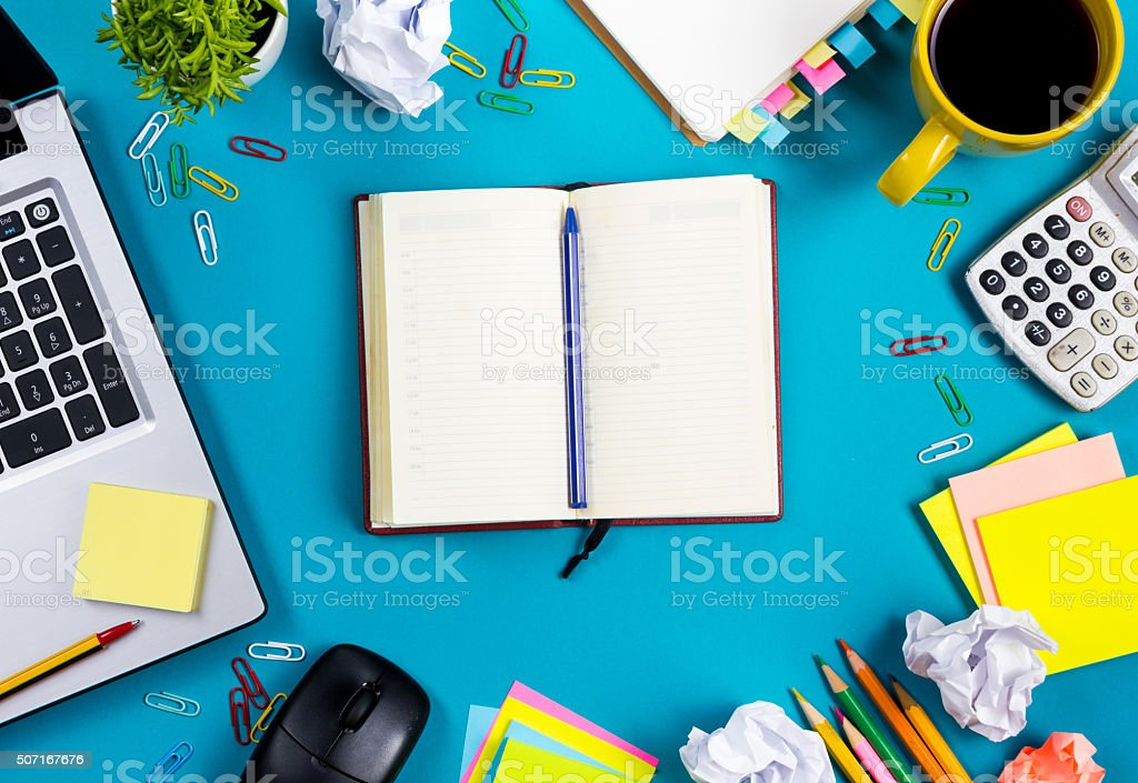 Office table desk with set of colorful supplies, white blank stock photo