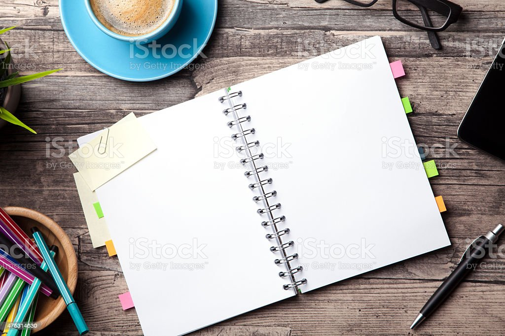 Office table with a coffee cup and a blank notepad stock photo