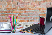 Office table with laptop, color pencil  over brick wall background