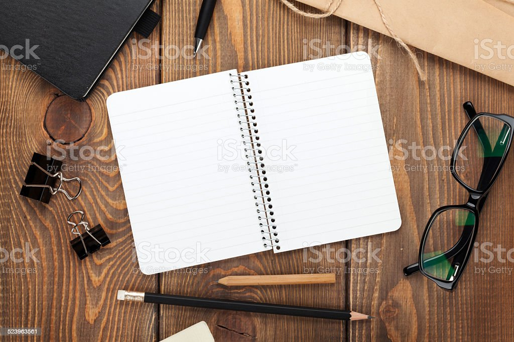 Office table with notepad, vintage envelope and supplies stock photo