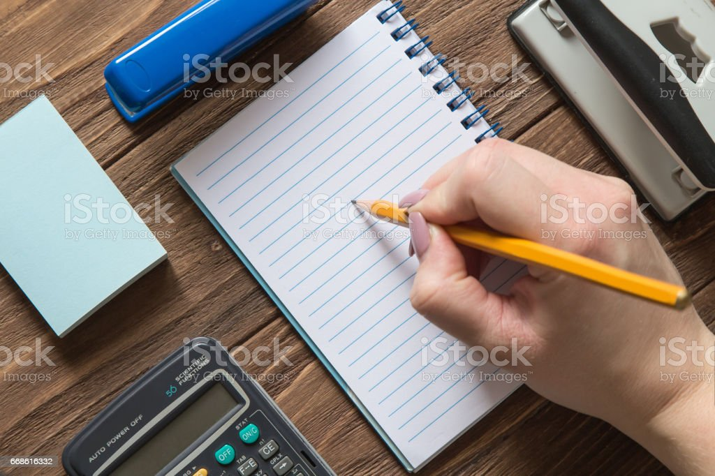 Office tools with womans hand holding a pencil stock photo