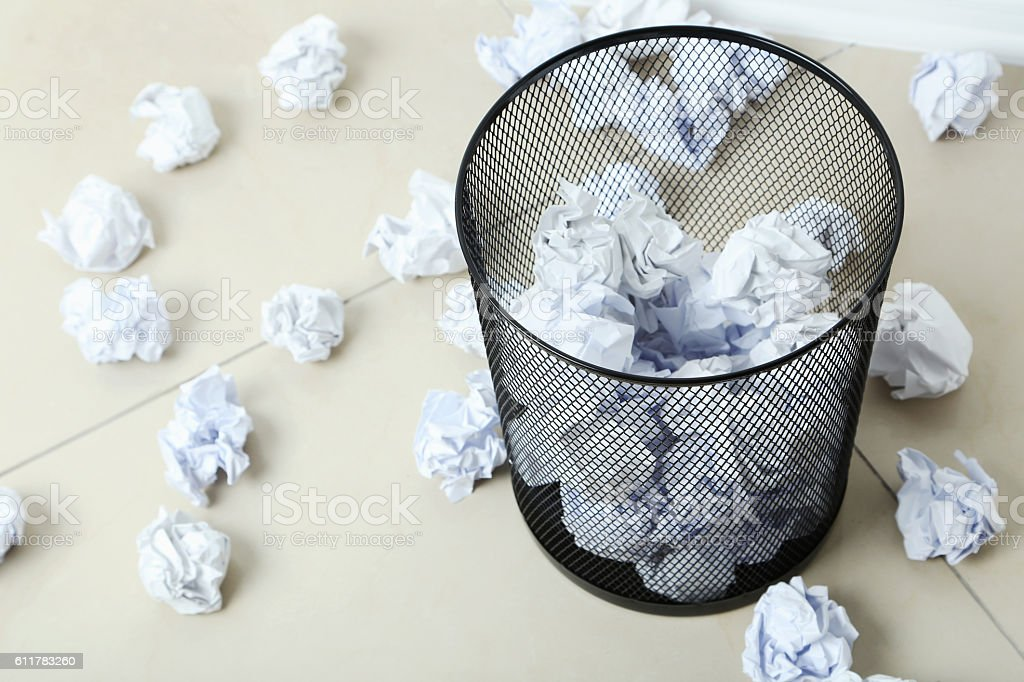 Office trashcan with crumpled paper balls stock photo