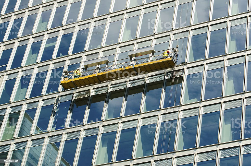 office window cleaners on a crane stock photo