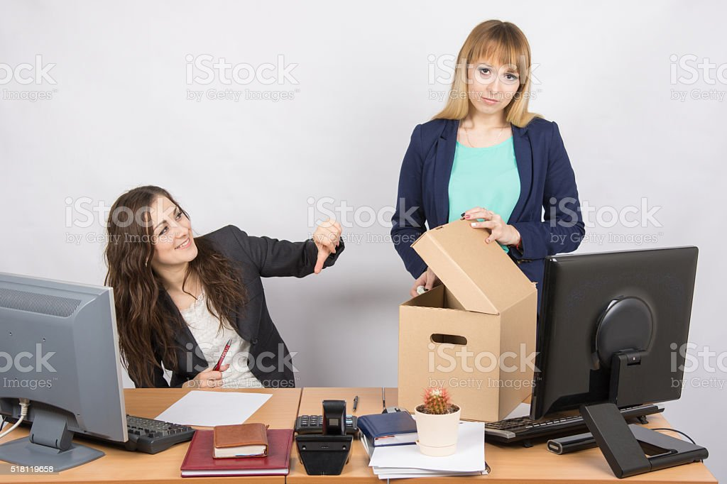 Office woman with a humiliating gesture unsettled the dismissed colleague stock photo