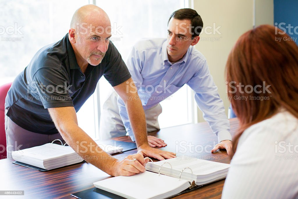 Office worker aggressively makes a point during meeting stock photo
