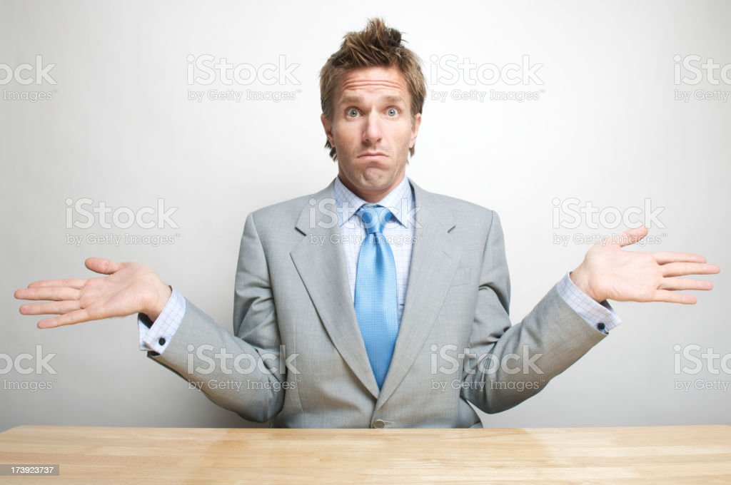 Office Worker Businessman Shrugging in Surprise at Desk royalty-free stock photo