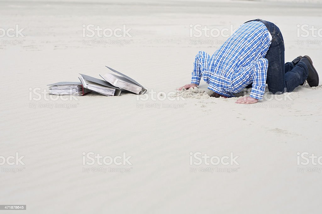 office worker hiding head in sand stock photo