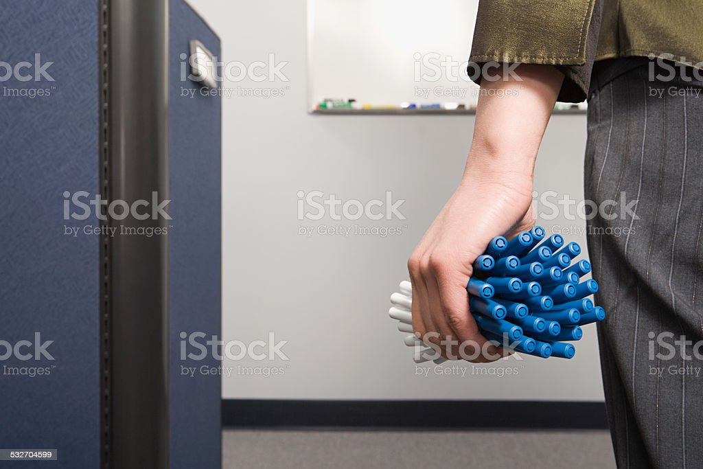 Office worker holding lots of pens stock photo
