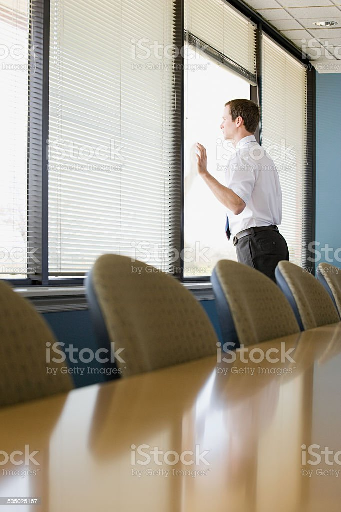 Office worker looking through window stock photo