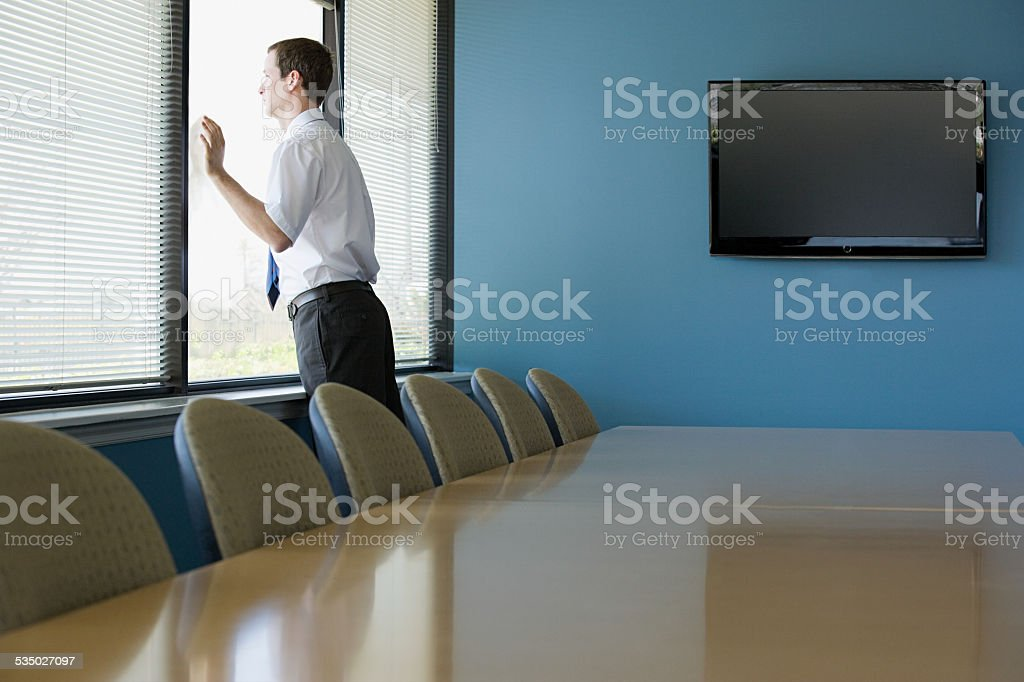 Office worker looking through window stock photo