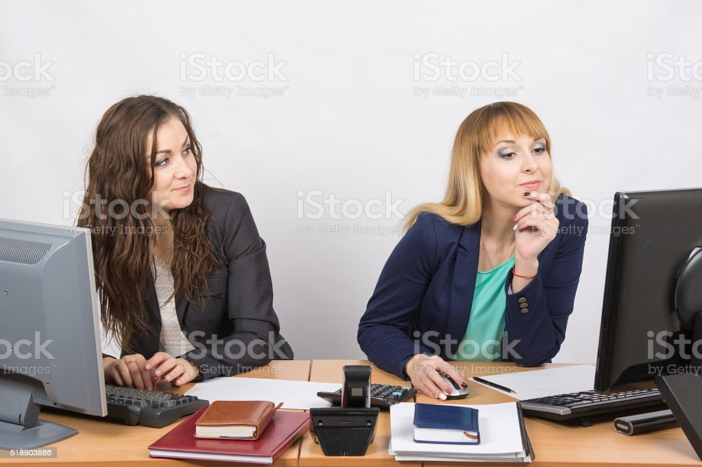 Office worker looking with distaste at the colleague sitting next stock photo