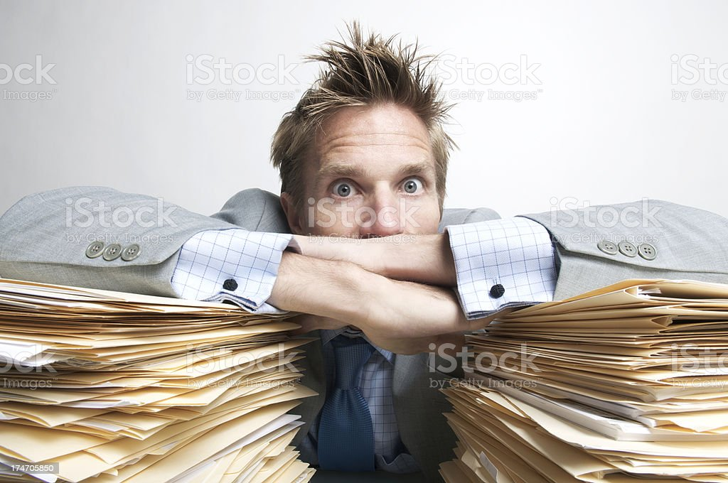 Office Worker Looks Overwhelmed on Paperwork royalty-free stock photo