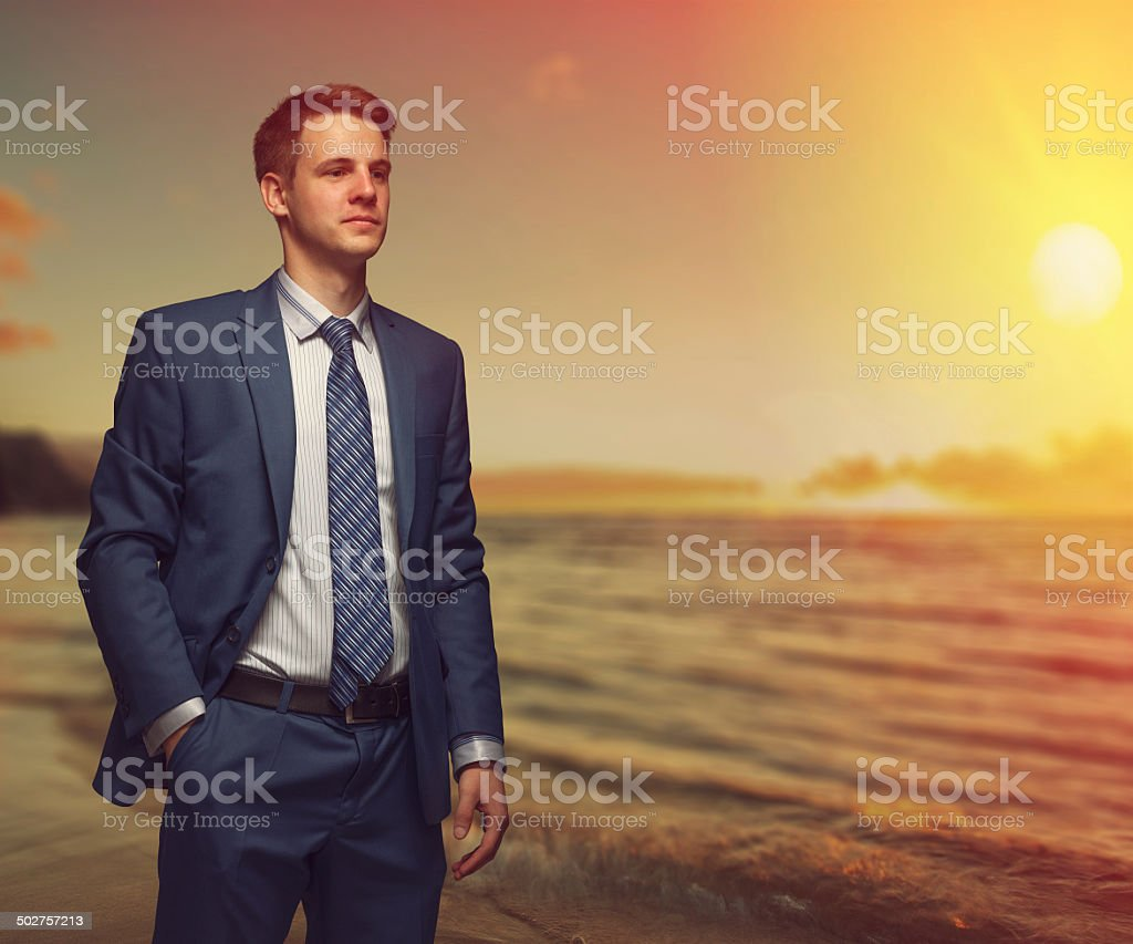 Office worker on the beach during sunset. stock photo