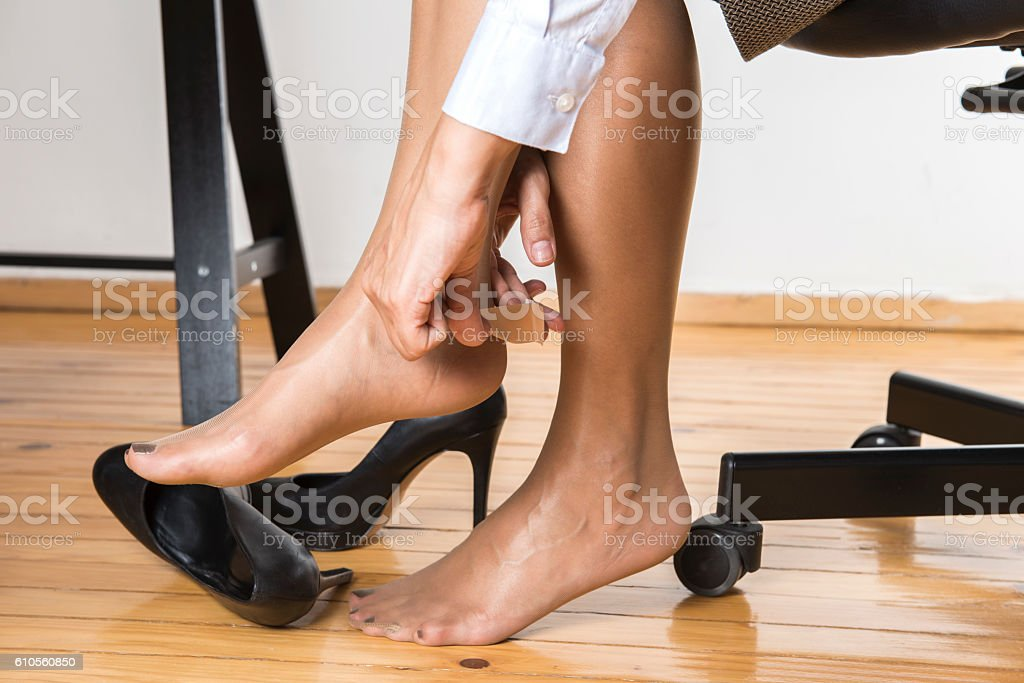 Office Worker Putting Adhesive Plaster On Heel stock photo