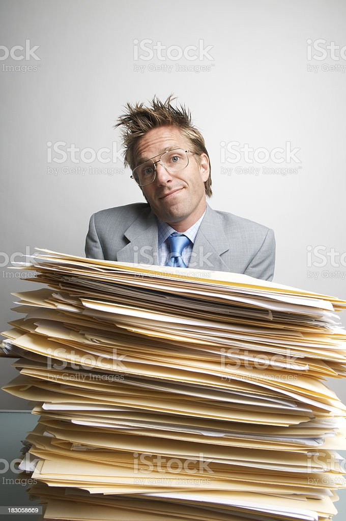 Office Worker Resigns Himself to Massive Stack of Paperwork royalty-free stock photo