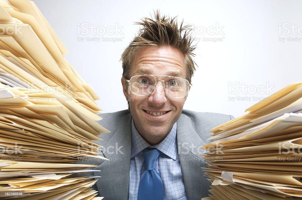 Office Worker Smiles between Piles of Paperwork stock photo