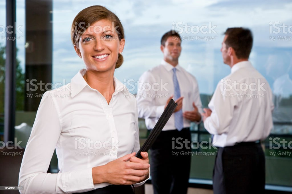 Office worker smiling, colleagues in background royalty-free stock photo