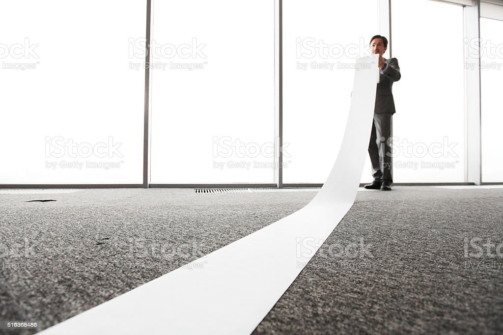 Office worker unrolling long sheet stock photo