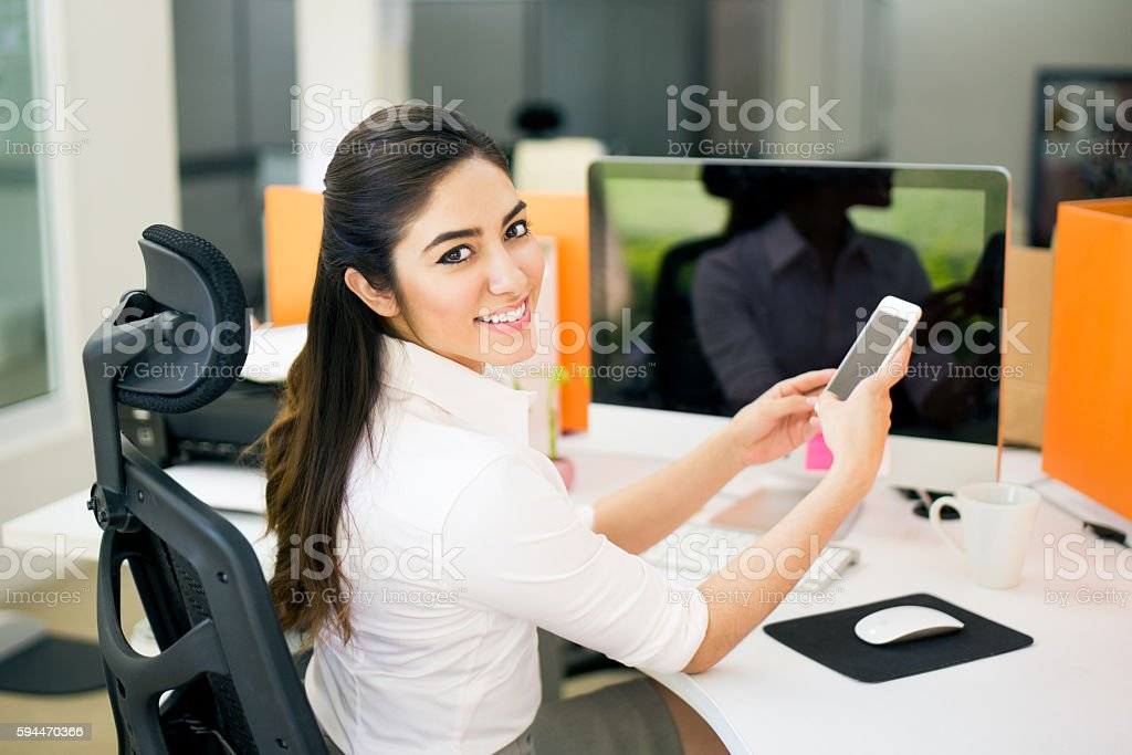 Office worker using smartphone and smiling at camera stock photo