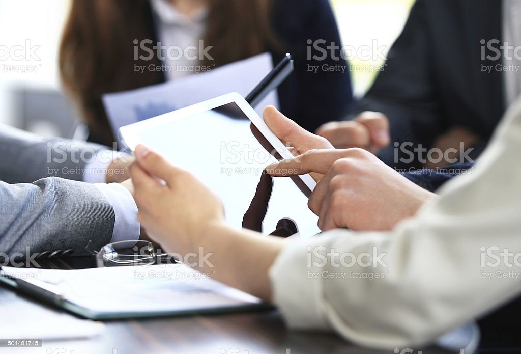 Office worker using tablet PC with co-workers stock photo