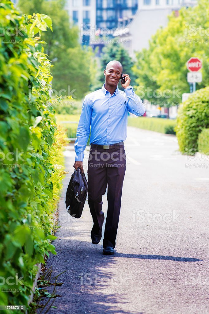 Office worker walking back home phone in hand, smiling, as if talking...