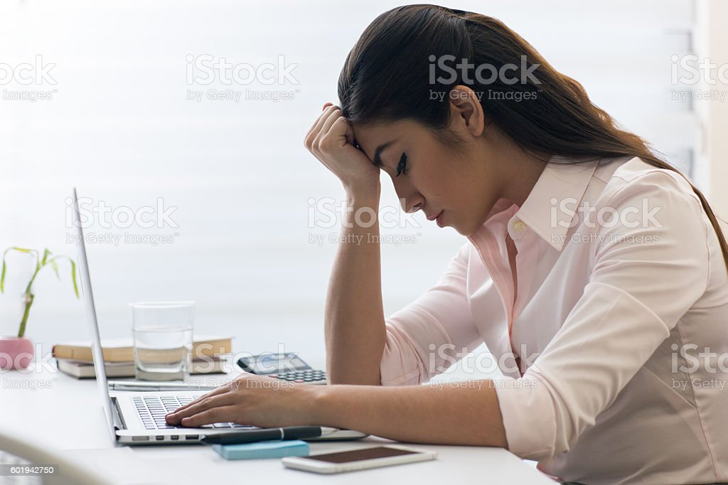 Office worker with head down and eyes closed stock photo