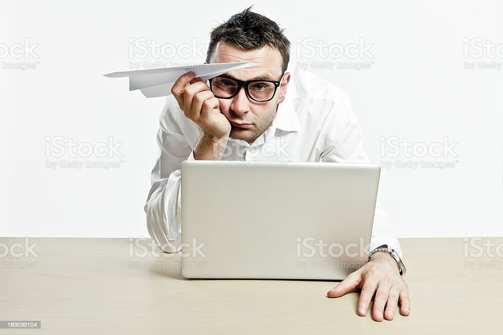 Office worker with laptop and paper plane is boring stock photo