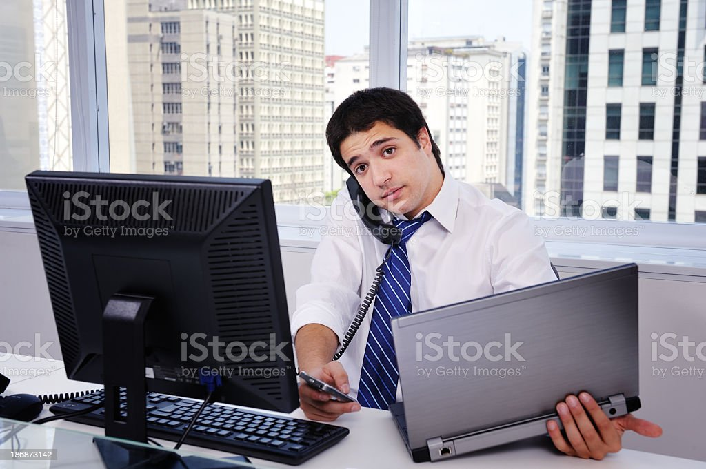 Office worker with multiple computers and phones in office stock photo